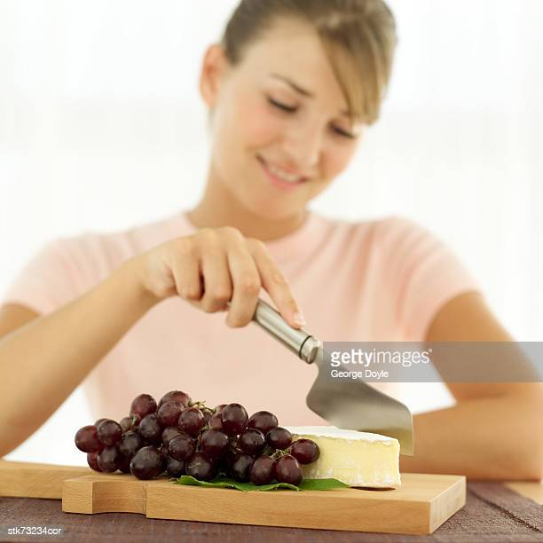 portrait of a woman cutting off a piece of cheese lying beside a bunch of grapes