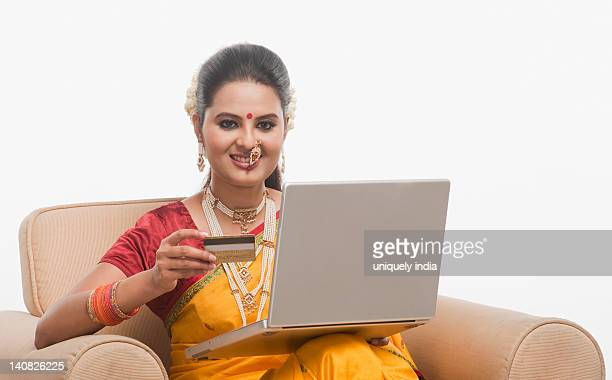 Portrait of a woman doing online shopping with a laptop on a traditional festival