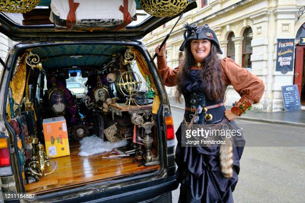 Portrait of a woman dressed in the steampunk style next to her van decorated with details of the same theme on Harbor Street in Oamaru considered the...