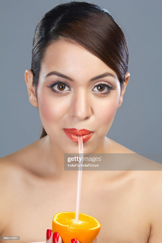 Portrait of a woman drinking juice from an orange : Stock Photo