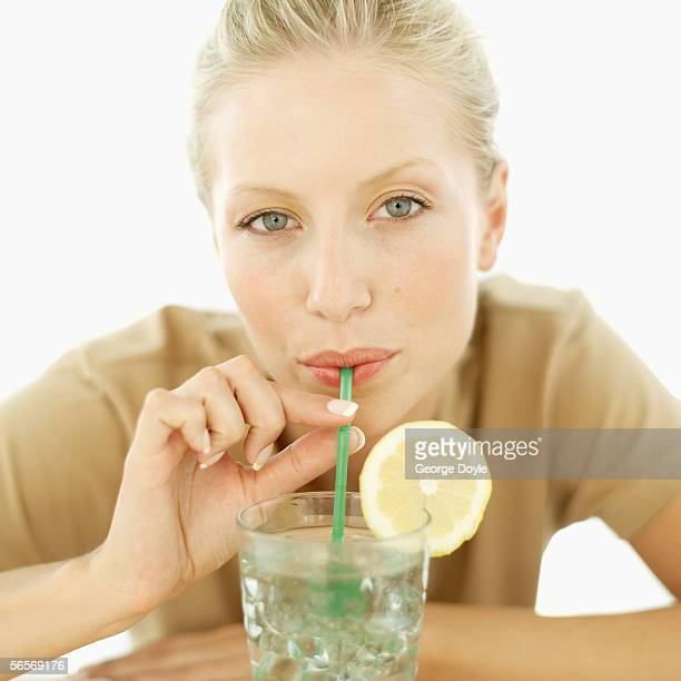 portrait of a woman drinking lemonade with a drinking straw