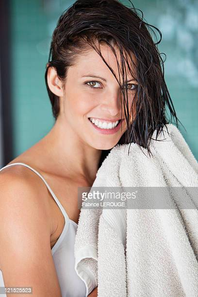 Portrait of a woman drying her hair with a towel