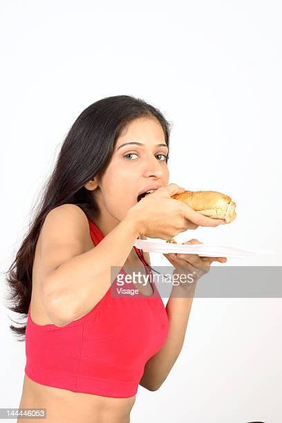 Portrait of a woman eating a hotdog