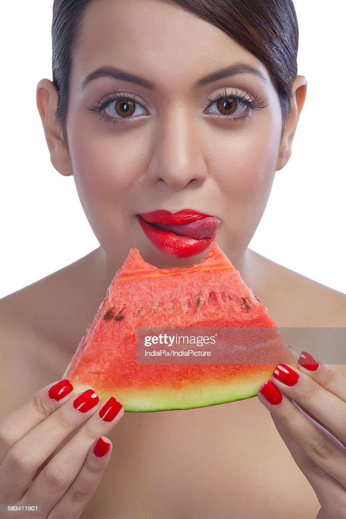 Portrait of a woman eating a watermelon : Stock Photo