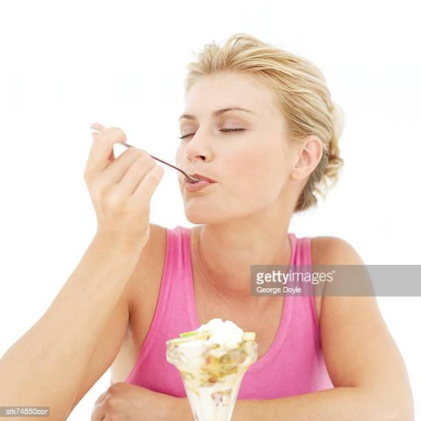 portrait of a woman eating an ice cream sundae with her eyes closed