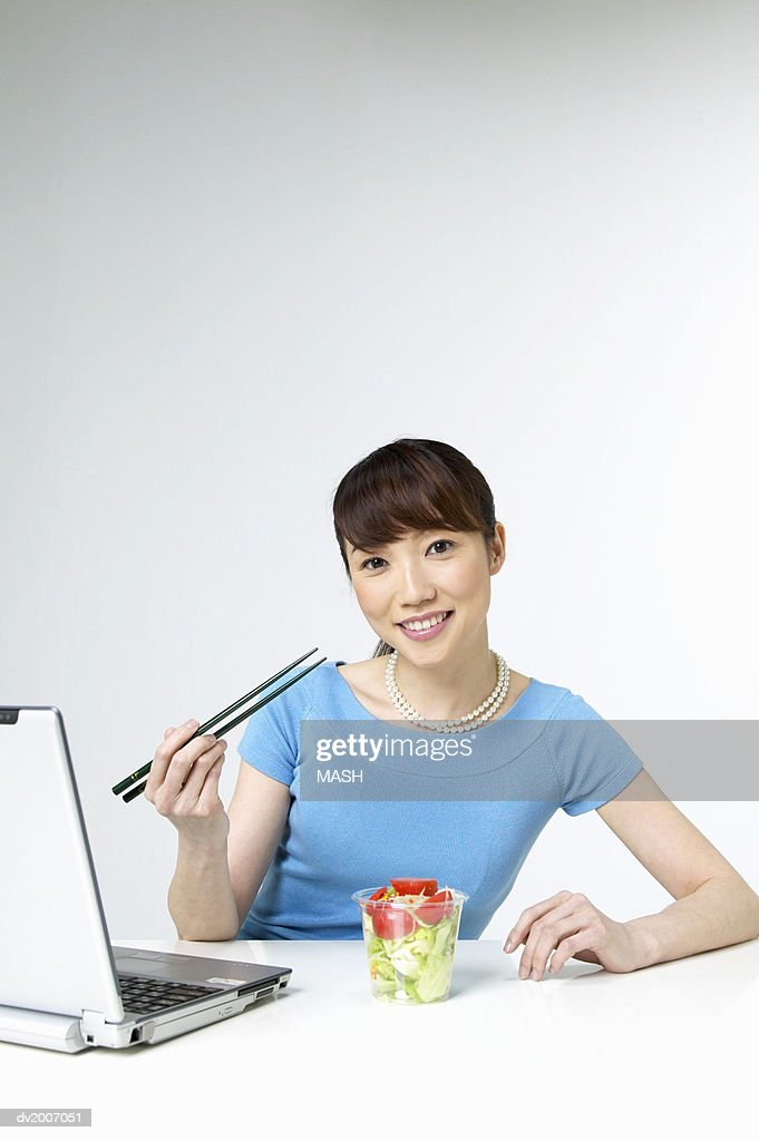 Portrait of a Woman Eating Salad With Chopsticks Sitting by a Laptop : Stock Photo