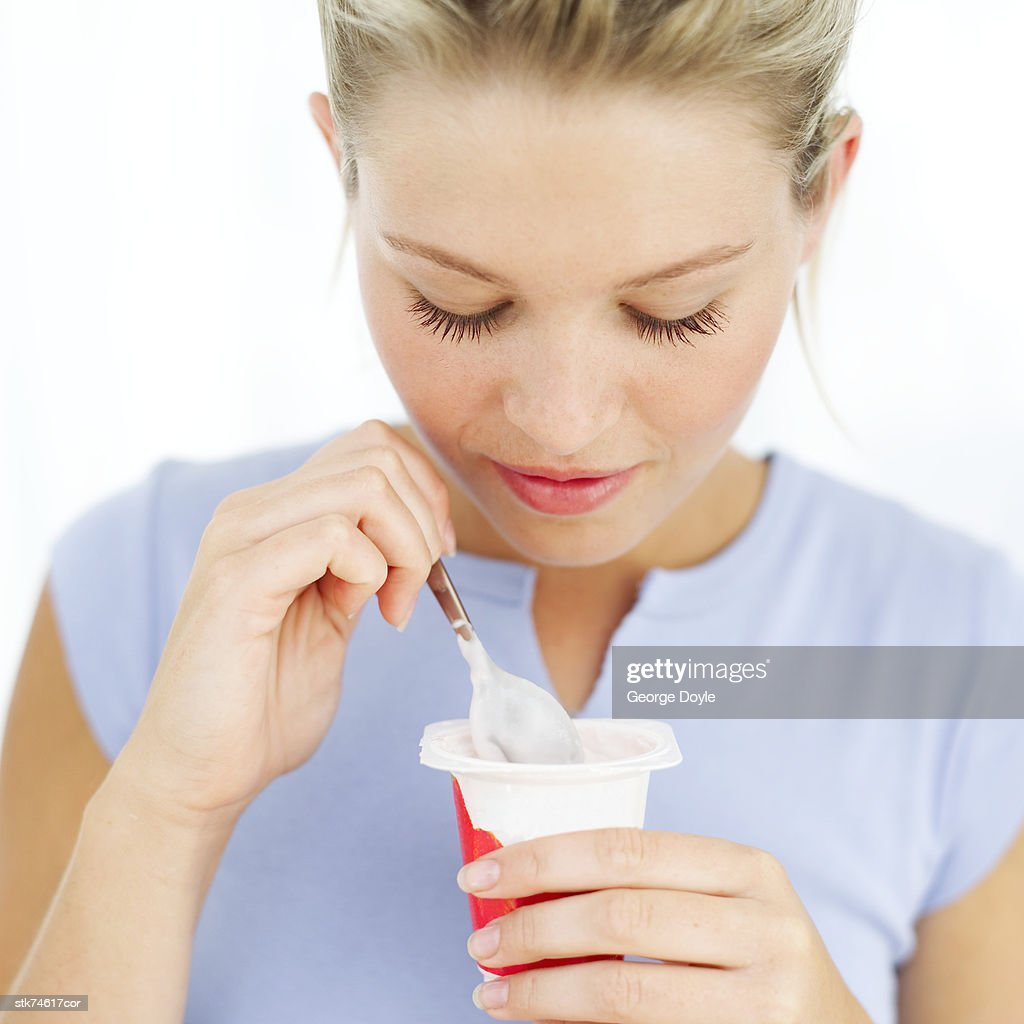 portrait of a woman eating yogurt : Stock Photo