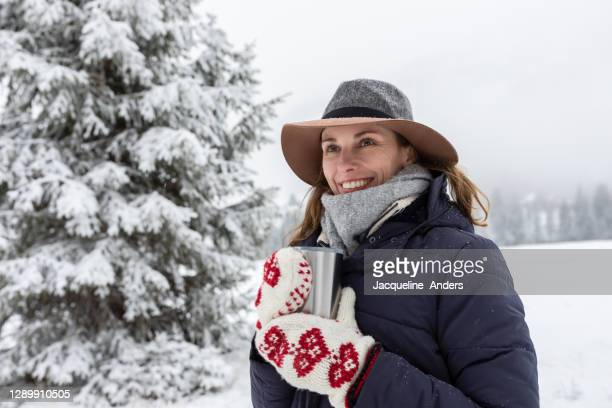 portrait of a woman enjoying hot coffee in the snow - hat stock pictures, royalty-free photos & images
