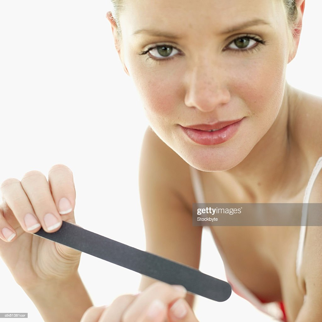 portrait of a woman filing her finger nails : Stock Photo