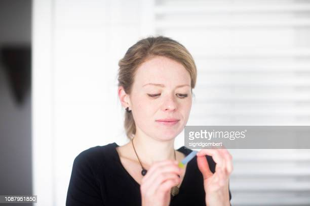 portrait of a woman filing her nails in the bathroom - self improvement stock pictures, royalty-free photos & images
