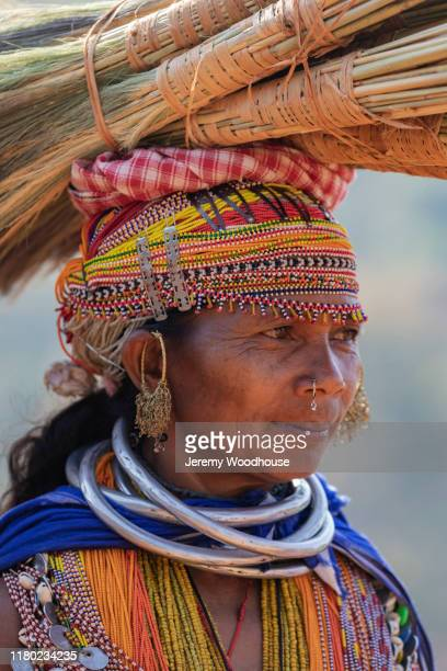 portrait of a woman from the bonda tribe carrying brooms to be sold at at the onokudelli market - jeremy woodhouse stock pictures, royalty-free photos & images