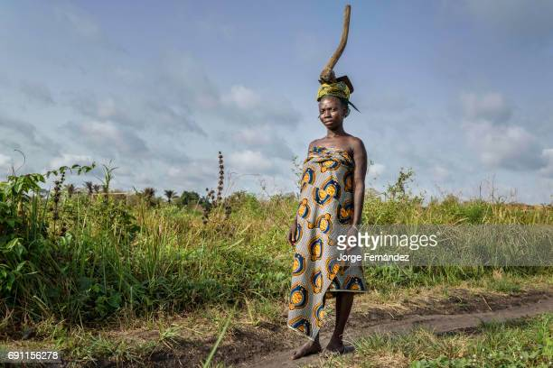 Portrait of a woman from the Holi tribe carrying a hoe on her head She is coming back from working in the fields Women in Africa are used to carry...