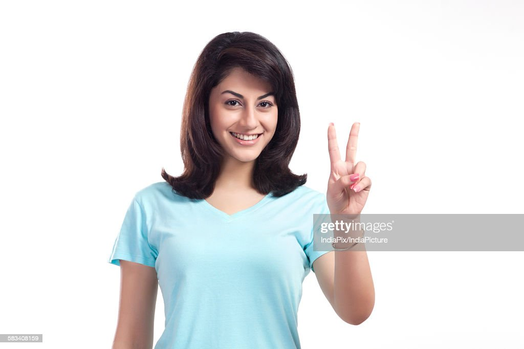 Portrait of a woman giving peace sign : Stock Photo
