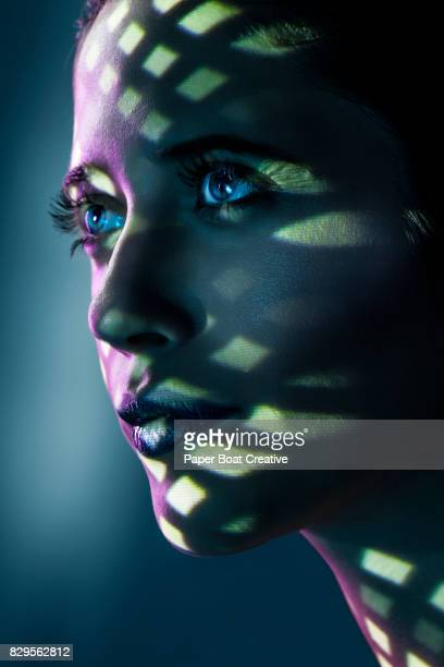 portrait of a woman hiding under a textured ceiling that forms different shapes and sizes of shadows that are reflected on her face - solo adulti foto e immagini stock