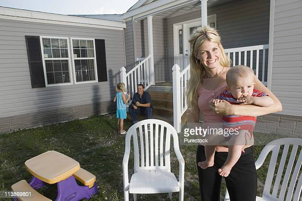 Portrait of a woman holding a baby in front of a trailer home