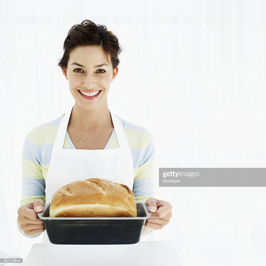 portrait of a woman holding a baking tray with freshly baked bread : Stock Photo