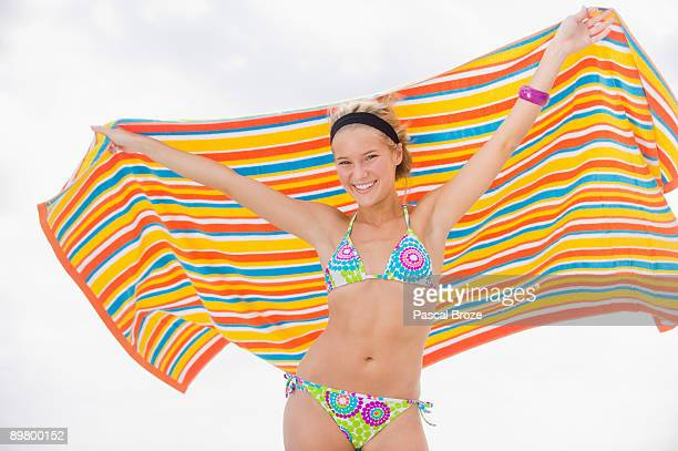 Portrait of a woman holding a beach towel and smiling