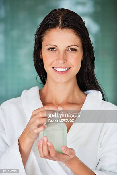 Portrait of a woman holding a bottle of aromatherapy oil and smiling