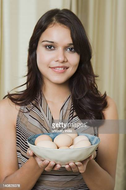 Portrait of a woman holding a bowl of eggs