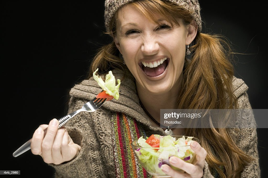 Portrait of a woman holding a bowl of salad and a fork : Foto de stock