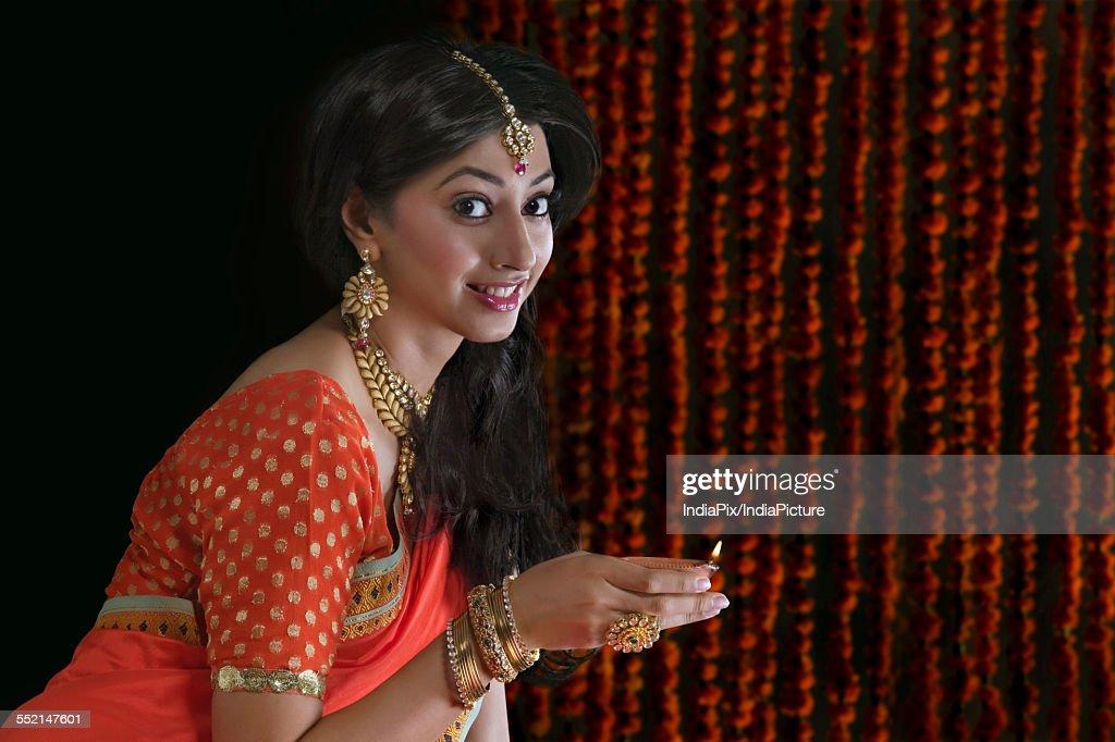 Portrait of a woman holding a diya : Stock Photo