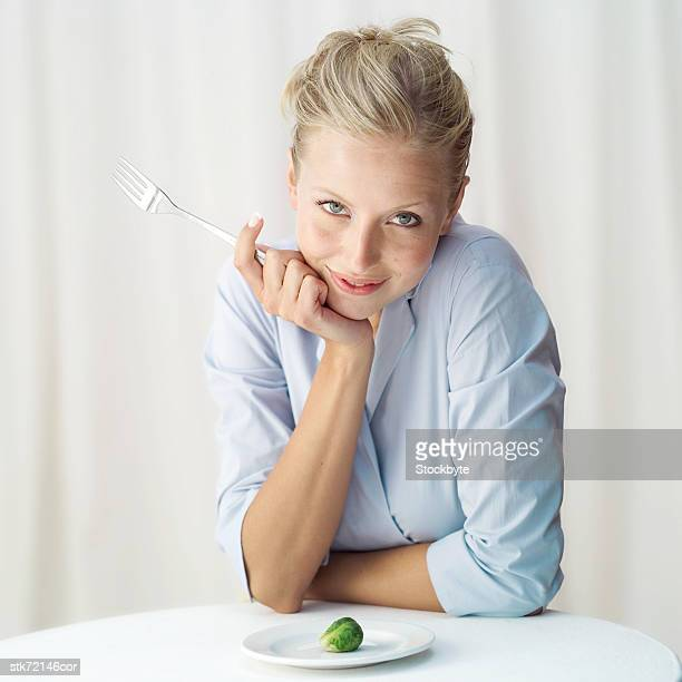 Portrait of a woman holding a fork with a Brussels sprout on a plate in front of her