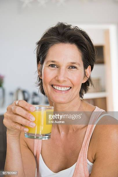 portrait of a woman holding a glass of juice - one mature woman only stock-fotos und bilder