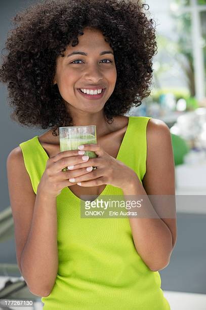 Portrait of a woman holding a glass of kiwi juice