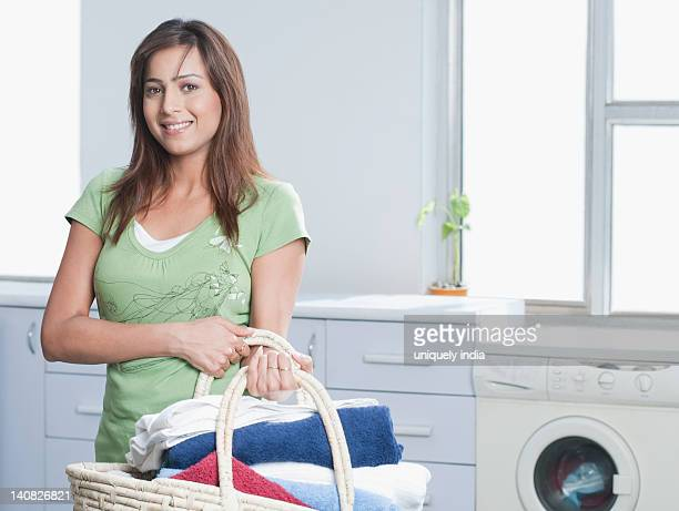 Portrait of a woman holding a laundry basket filled with towels