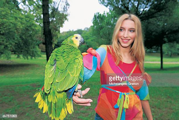 Portrait of a Woman Holding a Parrot in the Park