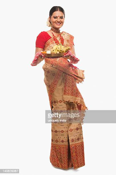 Portrait of a woman holding a plate of religious offerings on Bihu festival