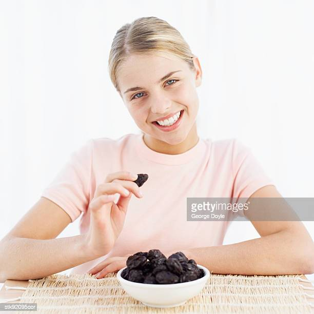 portrait of a woman holding a prune with bowl of prunes in front of her - dörrpflaume stock-fotos und bilder