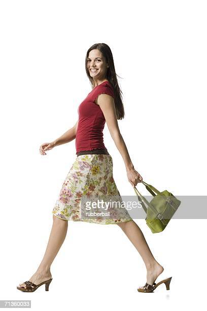 portrait of a woman holding a purse and smiling - striding stock pictures, royalty-free photos & images