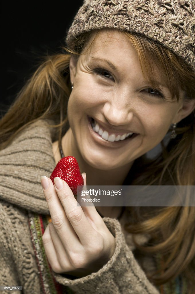 Portrait of a woman holding a strawberry smiling : Stockfoto