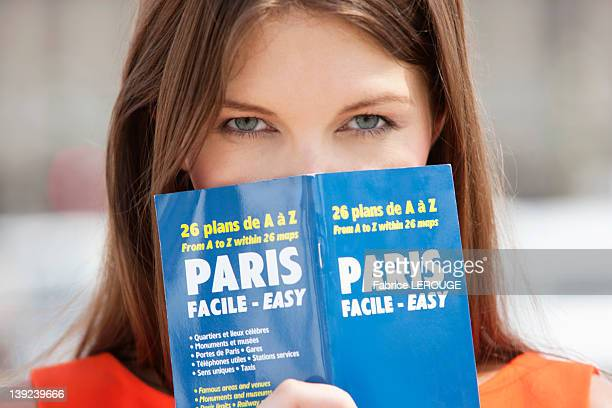Portrait of a woman holding a travel guidebook in front of her face, Paris, Ile-de-France, France