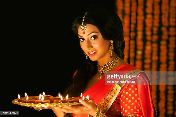 Portrait of a woman holding a tray of diyas