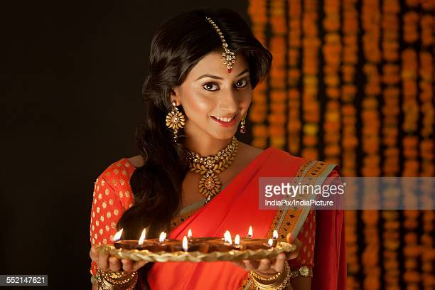 portrait of a woman holding a tray of diyas - necklace stock pictures, royalty-free photos & images