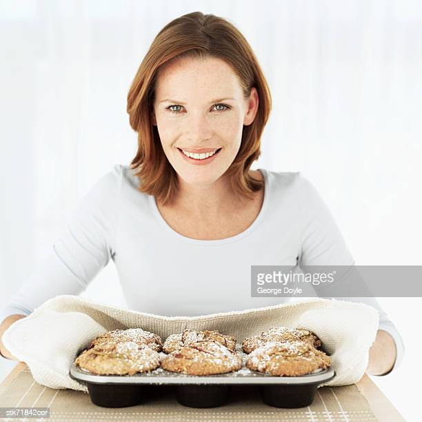 Portrait of a woman holding a tray of freshly baked muffins