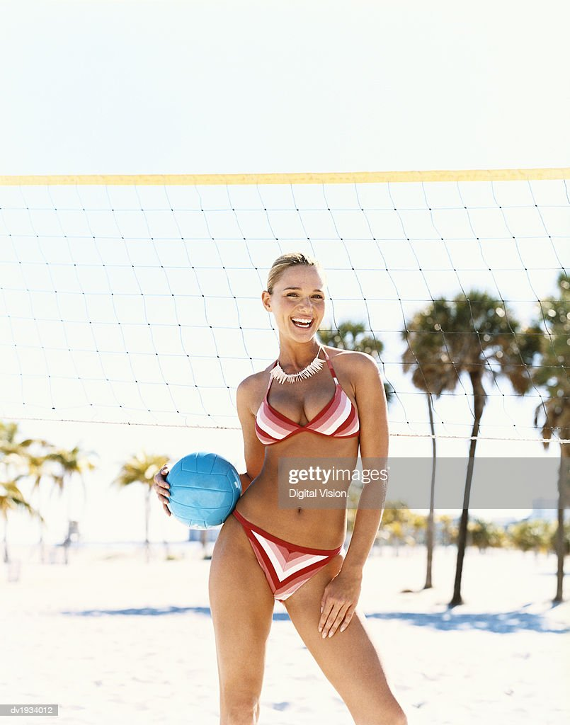 Portrait of a Woman Holding a Volleyball by a Sports Net on a Beach : Stock Photo