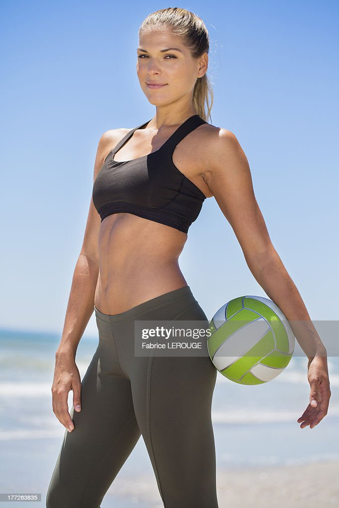 Portrait of a woman holding a volleyball : Stock Photo