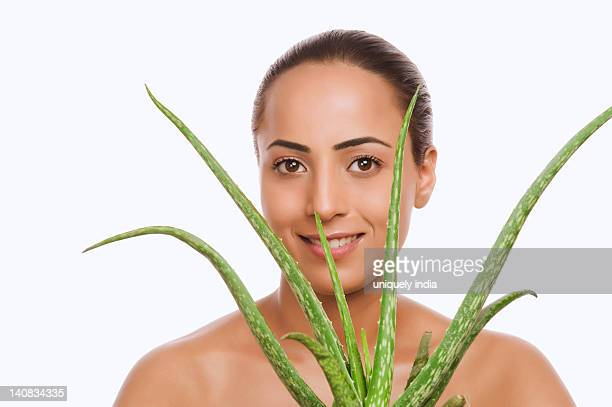 Portrait of a woman holding an Aloe Vera plant