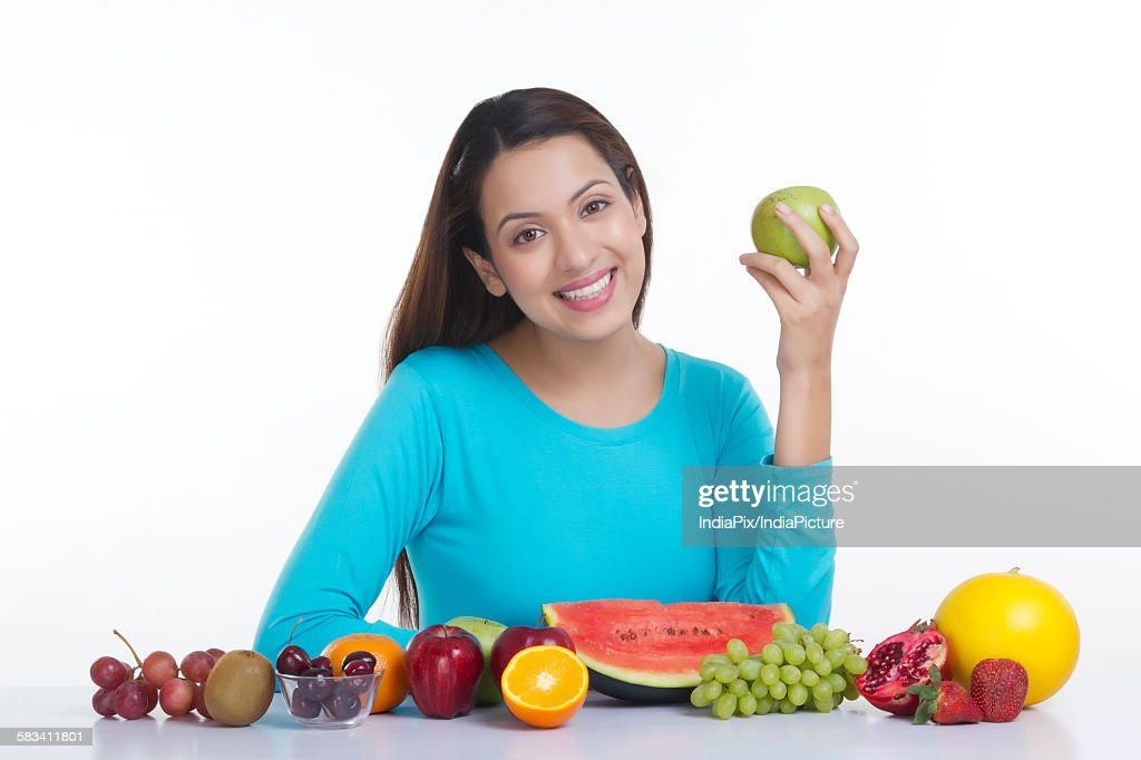 Portrait of a woman holding an apple : Stock Photo