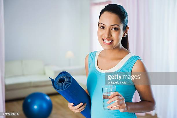 Portrait of a woman holding an exercise mat and glass of water