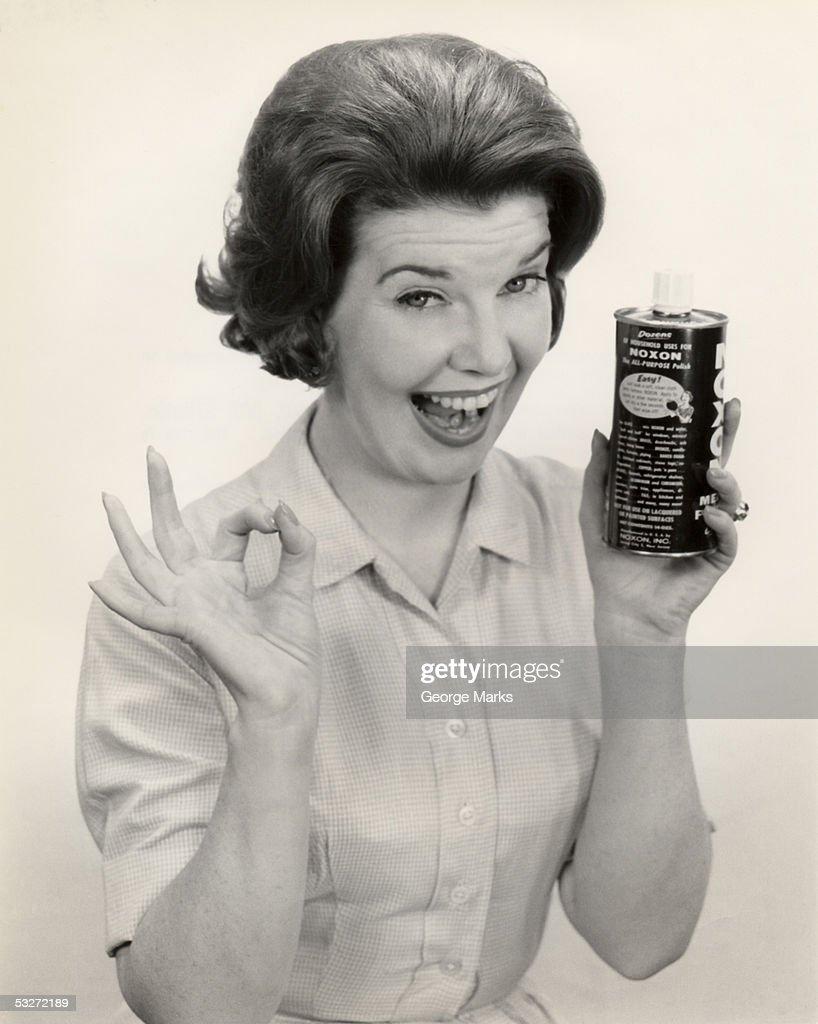 Portrait of a woman holding can of Noxon : Foto de stock