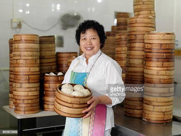 A portrait of a woman holding Dim Sum buns.