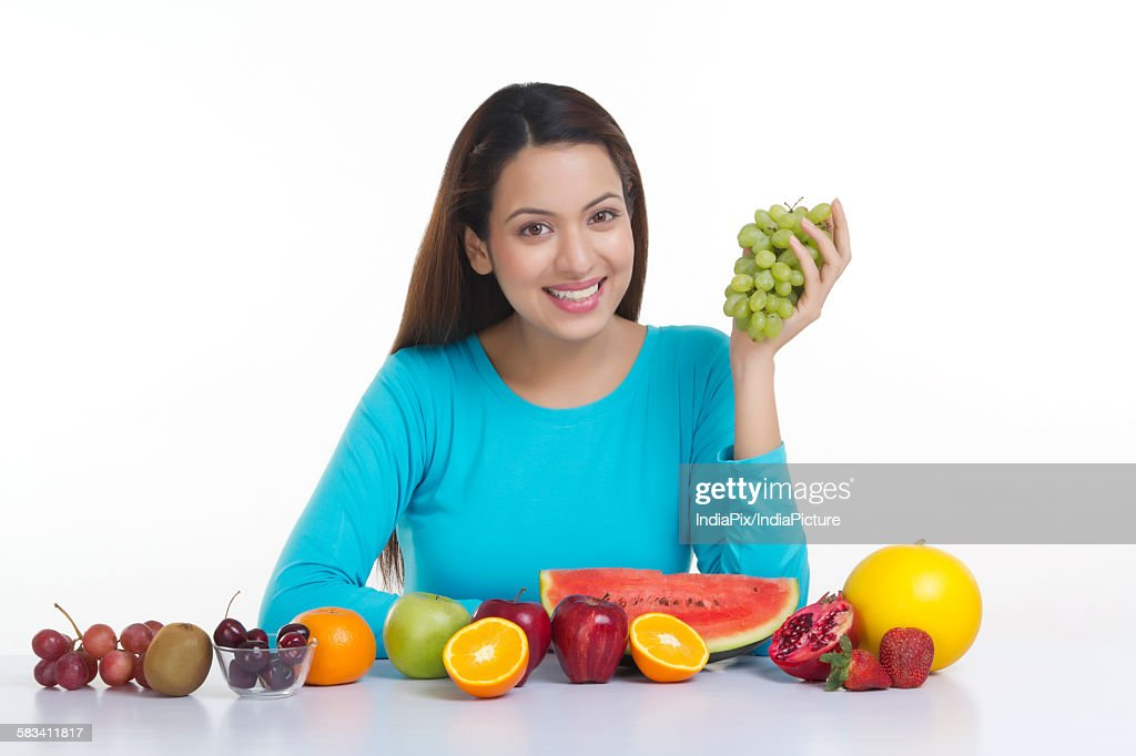 Portrait of a woman holding grapes : Stock Photo