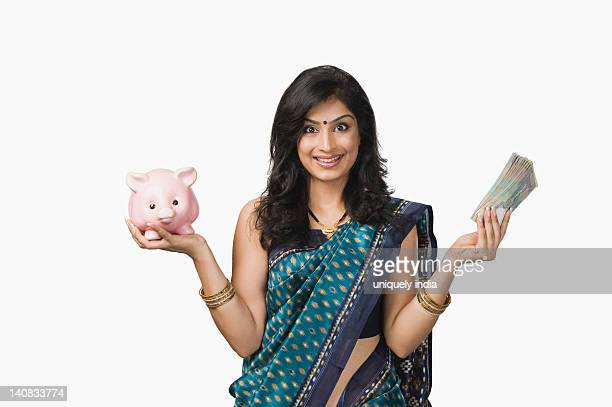 Portrait of a woman holding money and a piggybank