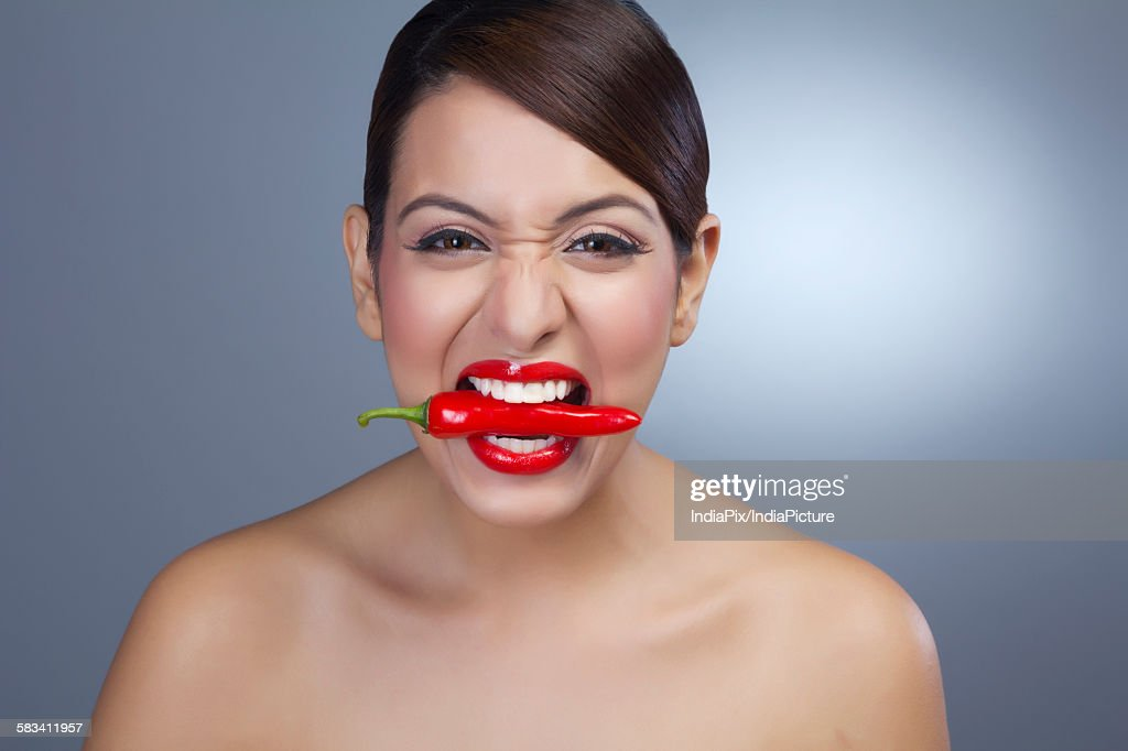 Portrait of a woman holding red pepper in teeth : Stock Photo