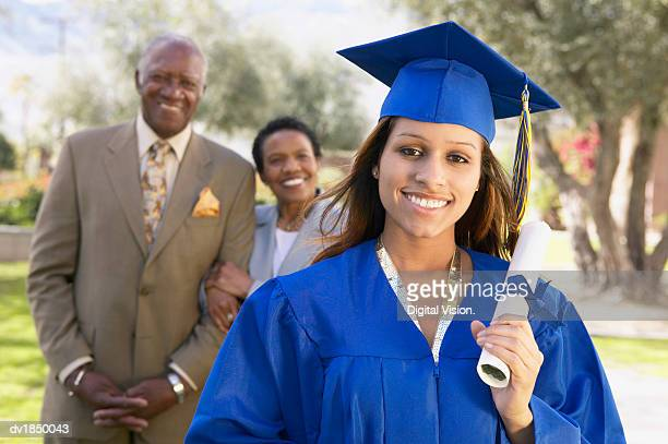 Portrait of a Woman in a Graduation Gown, Her Proud Parents Standing in the Background