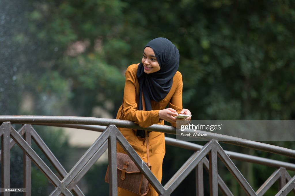 Portrait of a woman in a hijab on a bridge : Stock Photo